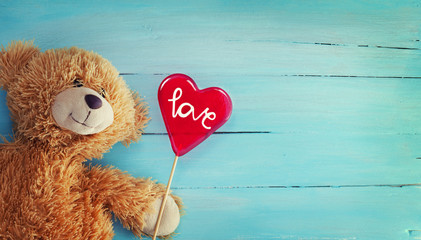 Cute Teddy Bear and Reda Candy Heart on Wood Background