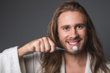 Healthy teeth. Portrait of smiling guy holding toothbrush in his hand. Isolated on grey background