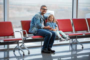 Enjoying rhythm. Full length of delighted middle-aged father and little daughter are sitting on airport bench while waiting for boarding. They are listening to music on smartphone through earphones