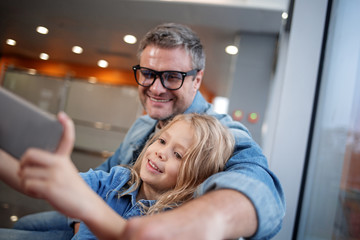 Selfie time. Positive adult father with pretty lovely daughter are sitting at terminal hall while little girl is taking picture of themselves using smartphone. Selective focus