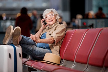 Pleasant conversation. Full length portrait of gray-haired lady in glasses is resting on seats at airport lounge while putting feet on suitcase. She is talking on mobile phone with smile. Copy space
