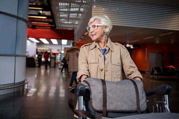 Positive senior charming woman in glasses is standing in modern terminal with airport trolley loaded with luggage. She is looking aside with smile. Copy space in the left side