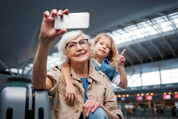 Lovely memories. Portrait of happy gray-haired granny is posing at international airport with her cheerful cute granddaughter. She is holding smartphone while looking at screen and taking photo