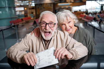 Our happy journey. Top view portrait of aged bearded man and charming old woman are standing together at airport lounge while looking at camera with joy. Gentleman is showing their ticket with smile