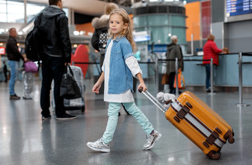 Favorite holiday. Full length portrait of optimistic trendy little girl is walking along airport lounge while carrying orange suitcase. She is looking at camera with slight smile. People in background