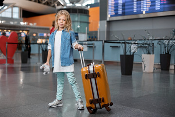First travel. Full length portrait of positive stylish cute blond child is standing at airport building and carrying her suitcase while keeping toy bear. She is looking at camera with joy. Copy space
