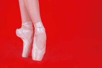 A Ballerina on the tiptoe on red background