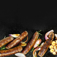 Grilled Sausages with Onion and Garlic Top View on BBQ Plate