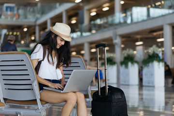 Asian woman teenager using laptop computer at airport terminal sitting with luggage suitcase and backpack for travel in vacation summer relaxing waiting flight transport