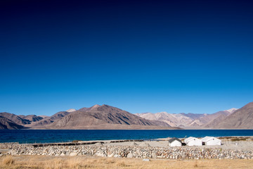 Landscape image of Pangong lake with small camps , mountains view and blue sky background