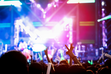 Hand gesture victory finger at concert stage lights crowd or audience artist band in the music festival rear view with spotlights glowing effect and people fan audience silhouette raising hands up