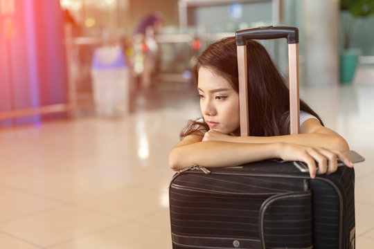 Asian woman waiting flight delay in airport hall her bored sitting wait long time early morning with baggage suitcase for travel transport