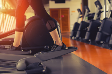 Exercise Elliptical cardio running workout at fitness gym of woman taking weight loss with machine aerobic for slim and firm healthy lifestyle in the morning.
