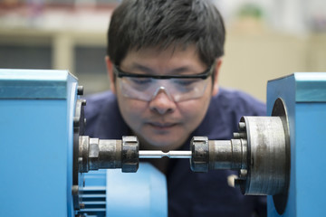 young asian engineer set up and testing test piece machine in the laboratory factory, engineering and industrial concept