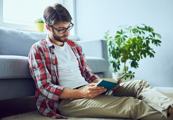 Relaxed man at home reading book