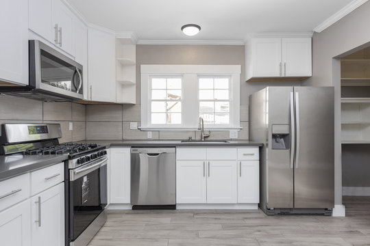 Kitchens in white new, with granite counter-tops, stove and stainless steel refrigerator.