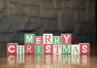 Wooden toy blocks with capital letters spelling Merry Christmas against a rock wall.