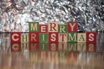Merry Christmas spelled with wooden toy blocks with capital letters photographed against against a silver background.