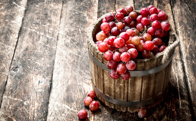 Red grapes in a wooden bucket.