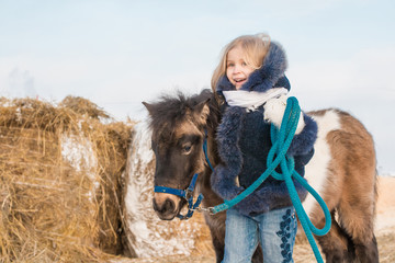 Small girl and small horse in a winter