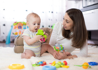 Funny baby and young woman playing in nursery. Happy family having fun with colorful toys at home.