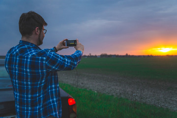 man taking picture of sunrise on highway