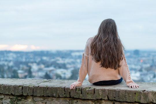 Junge Frau mit langen braunen Haaren vor der Skyline von Wiesbaden an einem Wintermorgen