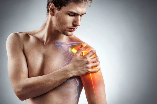 Man holding his injured shoulder that's highlighted in red. Medical concept.