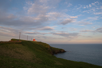 Kiritappu cape lighthouse on the rocky cliffs after sunset, Hokkaido, Japan