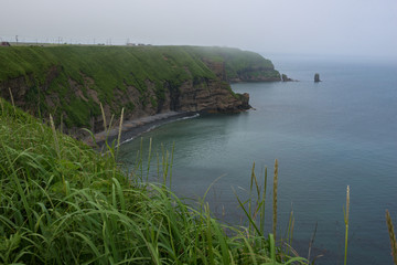 Green and steep rocky cliffs of Kiritappu cape, Hokkaido, Japan