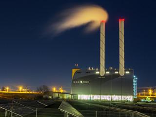 Kraftwerk bei Nacht mit Schornstein und Rauch