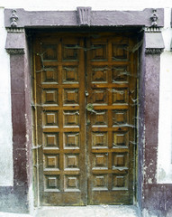 Solid wood door forming small squares, full of spider webs with signs of not having been used for a long time in a village on the Atlantic coast of La Coruna, Spain. Call Pontedeume