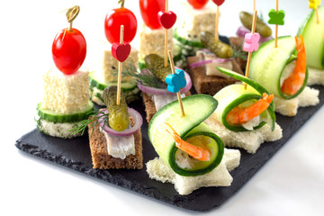 Snack canape with prawns, feta cheese and herring on rye bread on a slate board, isolate on a white background.
