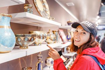 Tourist woman choosing ornamental ceramic dishes in souvenir shop