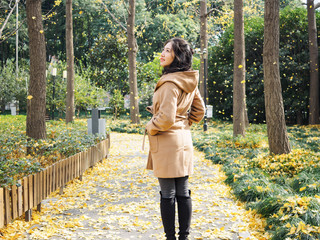 Portrait of a beautiful Chinese girl standing in the falling leaves in autumn park.