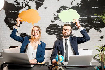 Couple of travel managers dreaming with colorful bubbles above the head sitting at the agency office with world map on the background