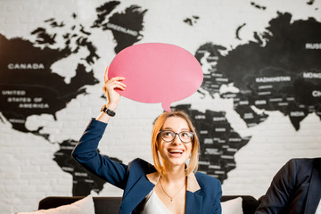 Young woman manager dreaming with colorful bubble above the head sitting at the office with world map on the background