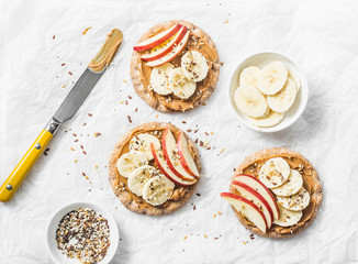 Peanut butter, apple, banana, flax and chia seed  crackers toast on a light background, top view