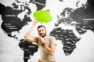 Man holding a colorful bubble above the head sitting at the office with world map on the background dreaming about traveling