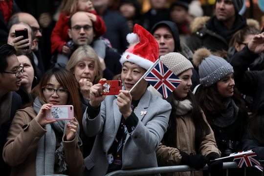 Spectators take photographs as dancers perform during the New Year's Day parade in London