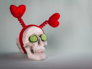Bizarre skull with two red hearts and cucumber slices. Healthy lifestyle concept.