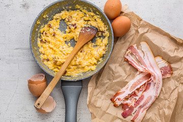 Ham and eggs. Scrambled eggs with bacon in ceramic pan