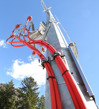steel pole with electric transformer and high voltage wires in a mountain place