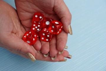 красные игровые кубики в куче на открытых ладонях рук