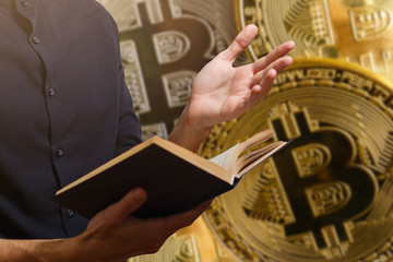 Male hands holding an crypto bible with bitcoin logo