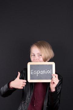 Schulind mit einem Schild auf dem Espaniol steht