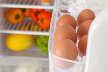 Raw eggs on refrigerator shelf, closeup