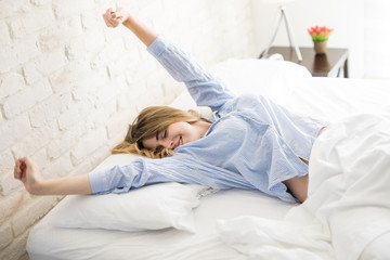 Optimistic girl waking up and stretching