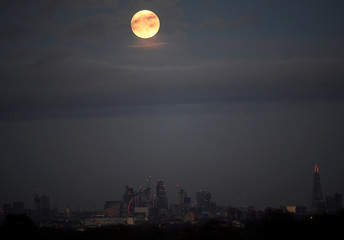 A 'supermoon' full moon is seen rising above the skyline of London