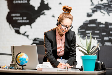 Portrait of a female travel agent in the suit and headset working indoors on the world map background